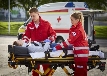 Ein Zivildiener und eine Mitarbeiterin im freiwilligen Sozialjahr betreuen eine Patientin auf der Trage.